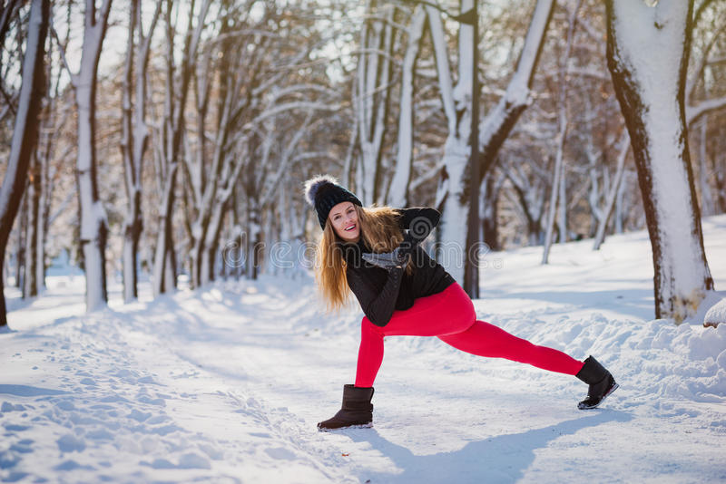 Beautiful woman doing yoga outdoors in the snow stock image