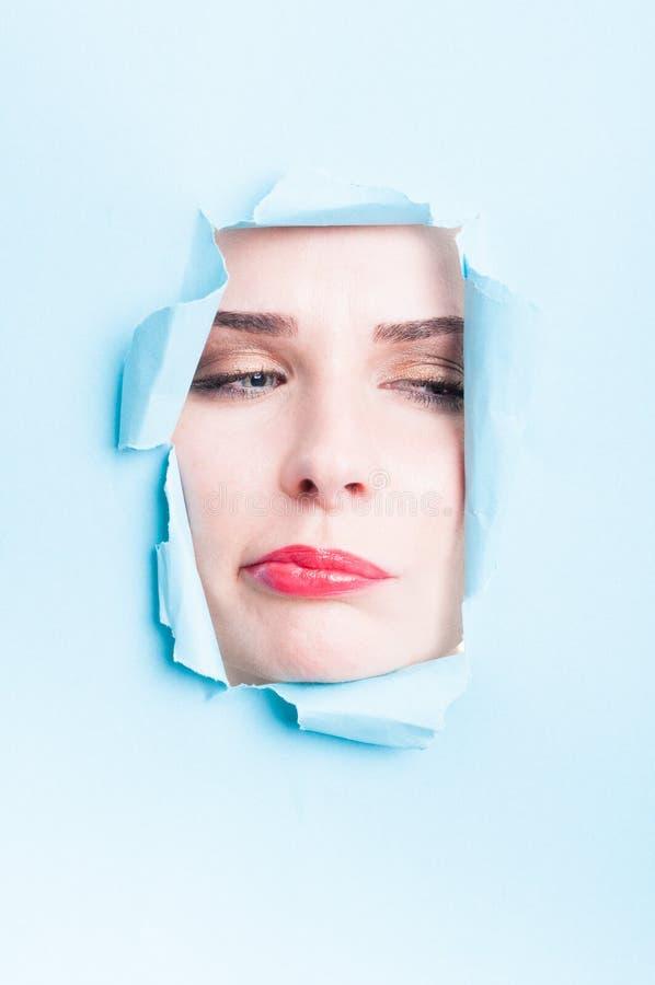 Beautiful woman doubt face with makeup thru torn cardboard. Beautiful woman doubt face with makeup thru torn blue or turquoise cardboard with copyspace royalty free stock photos