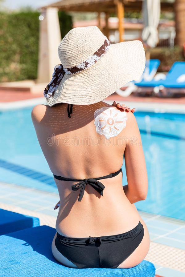 Beautiful woman with drawn sun by sun cream on her shoulder by the pool. Sun Protection Factor in vacation, concept.  royalty free stock photography