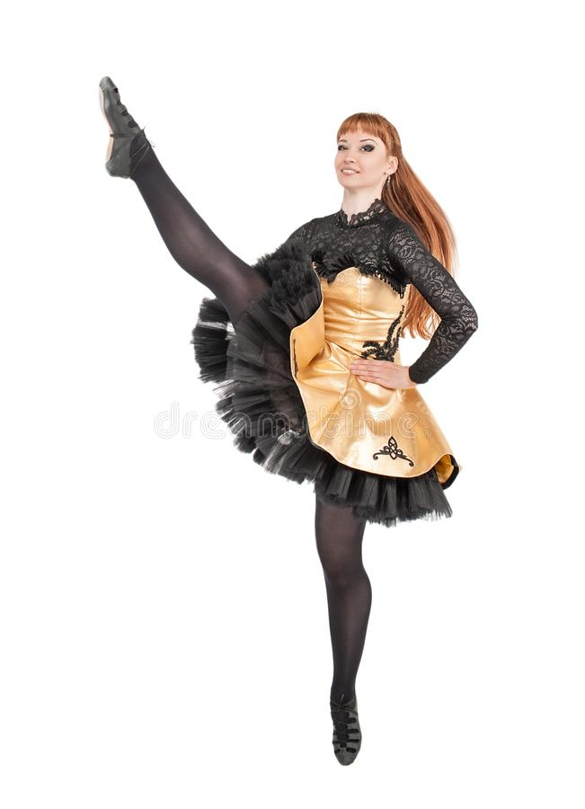 Beautiful woman in dress for Irish dance with leg up isolated. On white stock photo