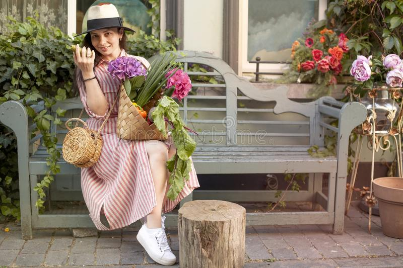 Beautiful woman in a dress with purchases, sits on a bench in the city street. A large basket of vegetables and flowers in the royalty free stock images