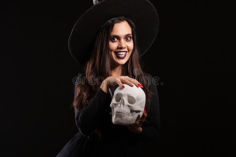 Beautiful woman dressed as witch for Halloween playing with a scary skull stock photo