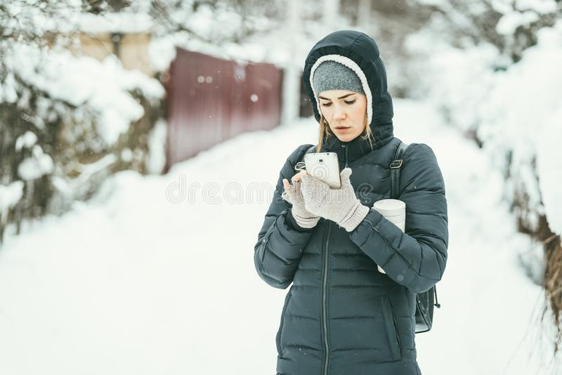 Beautiful woman dressed in a black winter jacket with mobile phone and thermos flask under her arm. Snow landscape royalty free stock photos