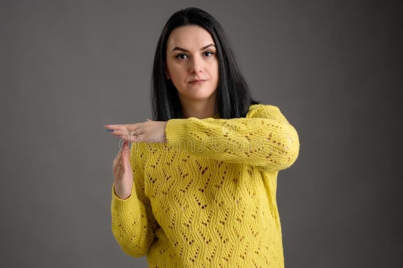 Beautiful woman dressed casually showing time out sign. Young woman with black hair dressed casually in a yellow sweater showing time out sign, posing an stock photo