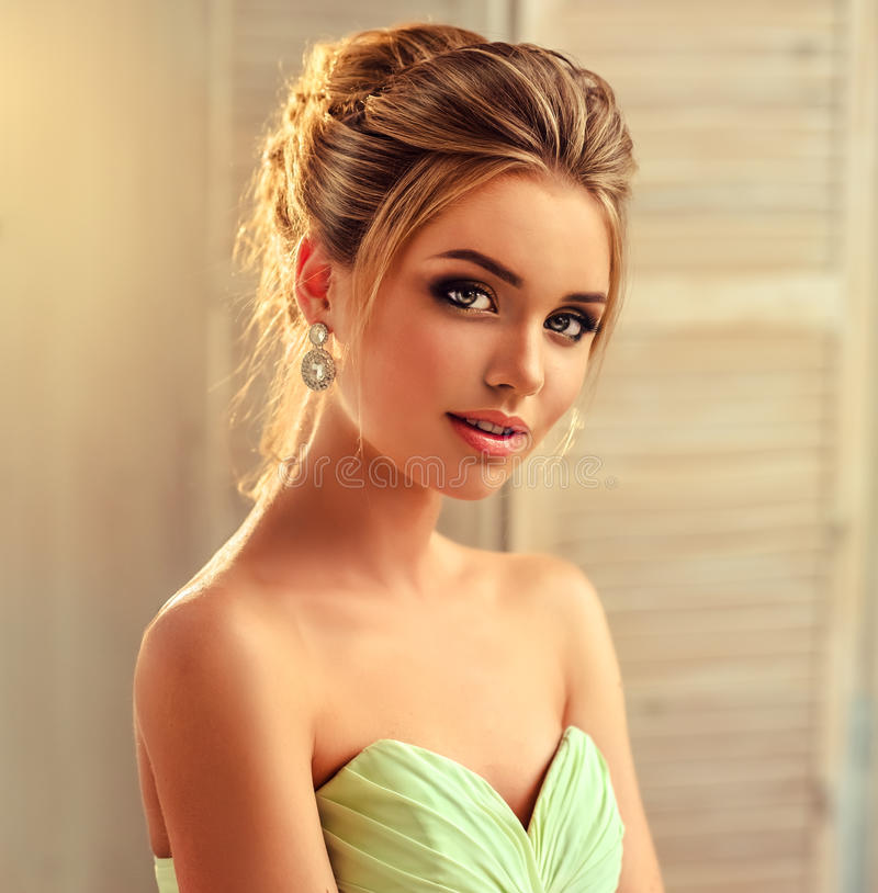 Young and attractive blond model dressed in evening gown and jewelry earings. royalty free stock image