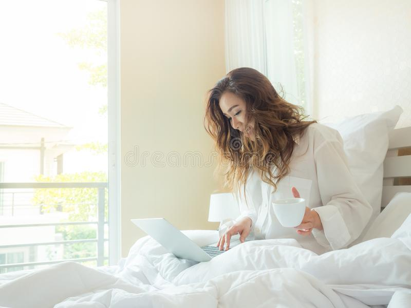 Beautiful woman is drinking coffee on the bed. And working with laptop stock photos