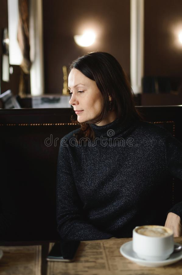 Beautiful woman drinking coffee in a cafe with a beautiful modern interior. Close-up stock images