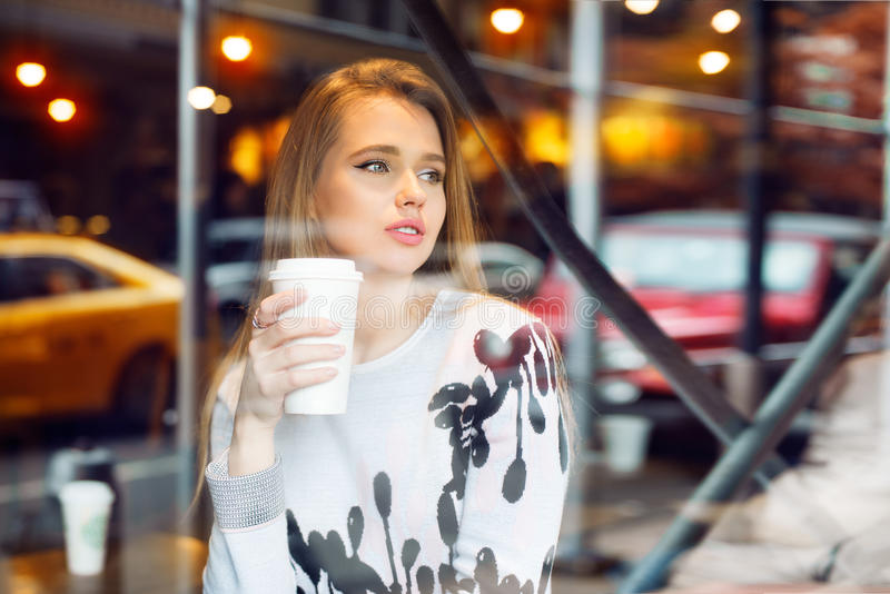 Beautiful woman drinking coffee in coffee shop from white paper coffee cup and looking to the city street through the window. Girl stock images