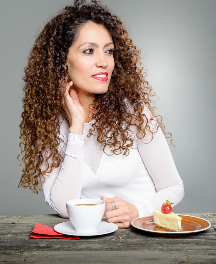 Beautiful woman drinking coffee. And eating cheese cake stock photos
