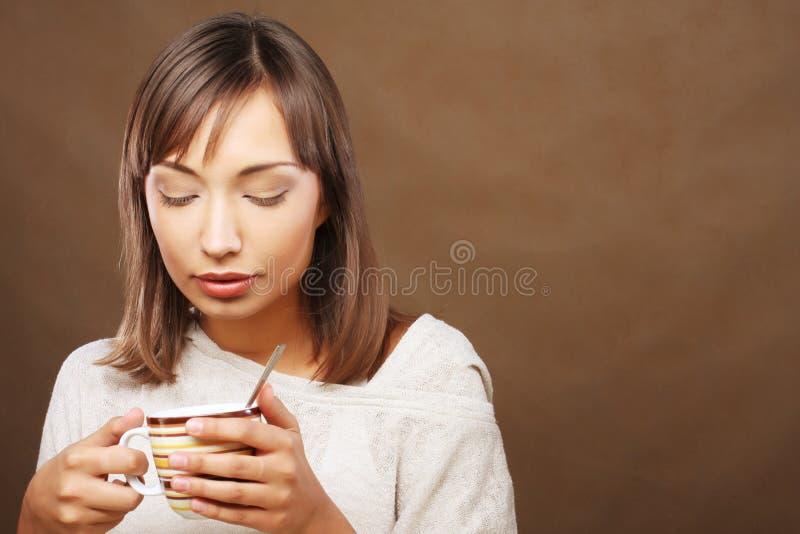 Beautiful woman drinking coffee. Beautiful smiling woman drinking coffee royalty free stock image
