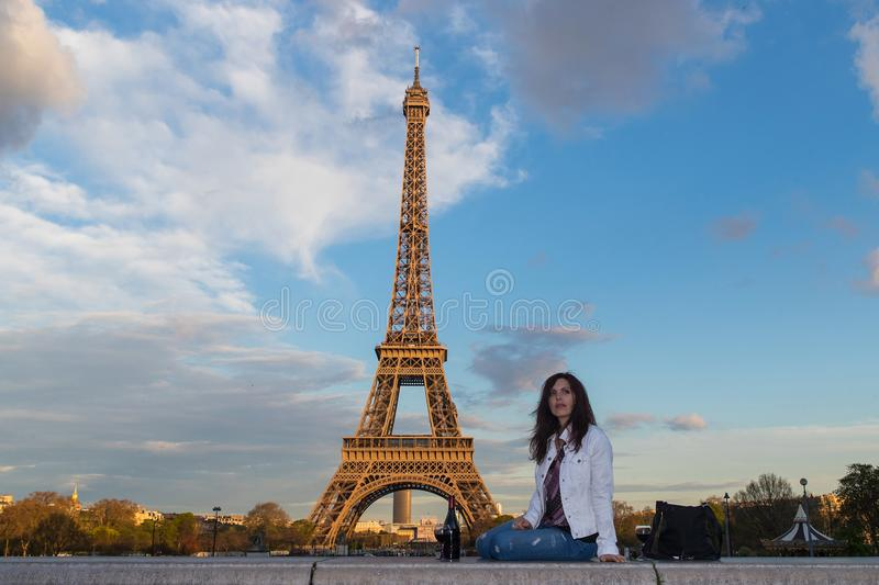 Beautiful woman drinking a glass of wine at the Eiffel Tower in royalty free stock image