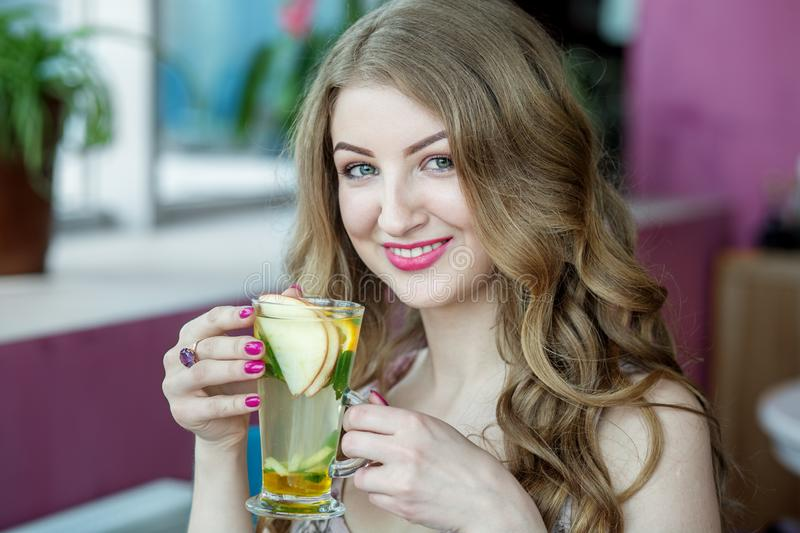 Beautiful woman drinking lemonade and smiling. Tea with mint and citrus. Concept of lifestyle, drinks and healthy eating stock photo