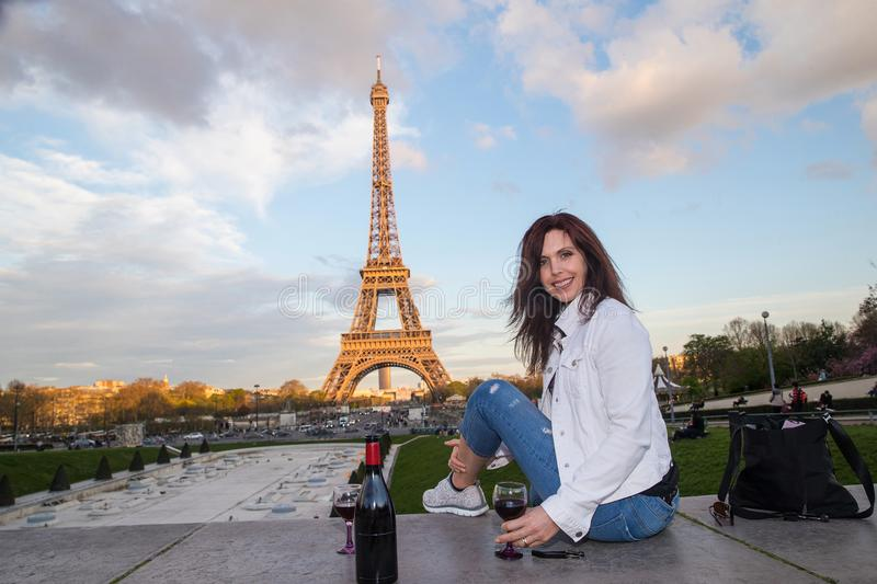 Beautiful woman drinking wine at the Eiffel Tower in Paris, Fran stock image