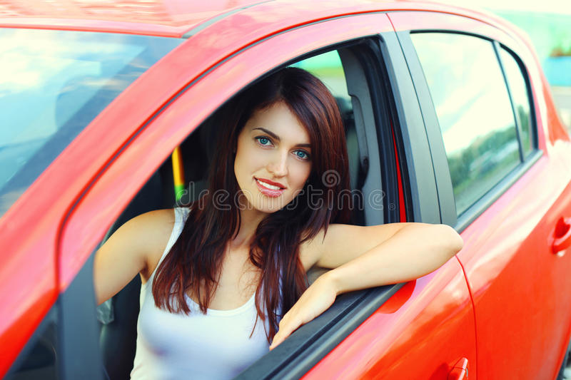 Beautiful woman driver behind the wheel red car. Beautiful young woman driver behind the wheel red car stock images