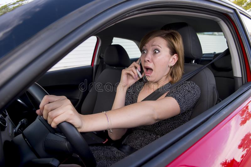 Beautiful woman driving car while texting using mobile phone distracted. Young beautiful woman driving car while texting and using mobile phone distracted in royalty free stock photo