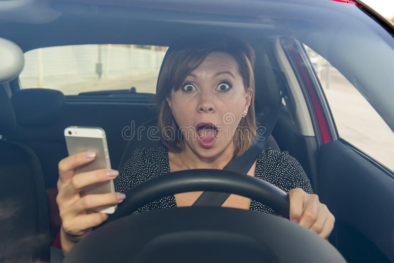 Beautiful woman driving car while texting using mobile phone distracted. Young beautiful woman driving car while texting and using mobile phone distracted in stock photography