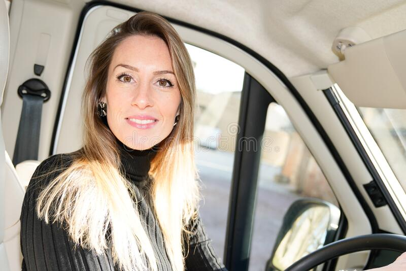 Beautiful woman driving motor home rv camping van driver smiling in driver seat lifestyle vanlife royalty free stock image
