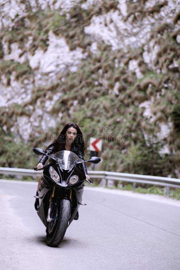 Beautiful woman driving a motorcycle royalty free stock photo