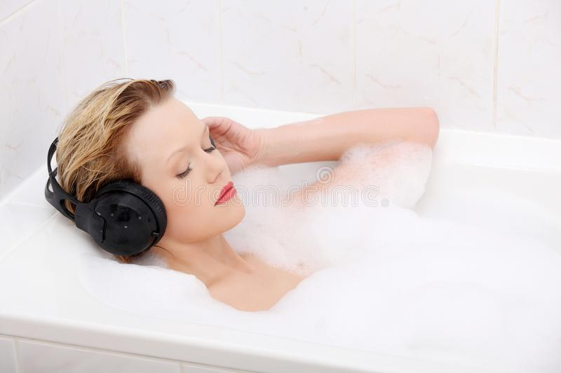 Beautiful woman with earphones in the bath. stock images