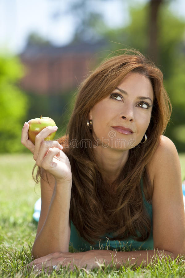 Beautiful Woman Eating An Apple & Thinking. A beautiful woman in her thirties laying down outside on grass holding or eating an apple looking up and thinking royalty free stock photos