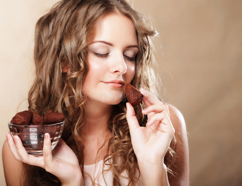 Beautiful woman eating a chocolate bonbon. Beautiful curly woman eating a chocolate bonbon royalty free stock photos