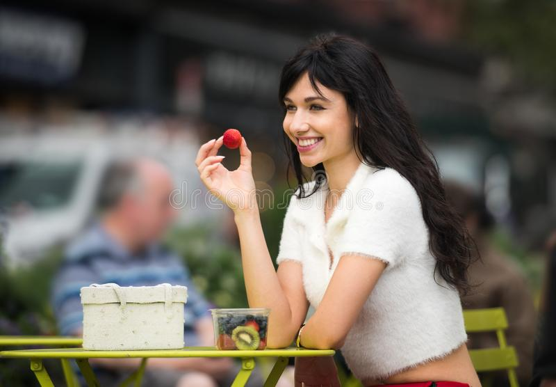Beautiful woman eating fruit lunch out of office on city street on public place. royalty free stock photography