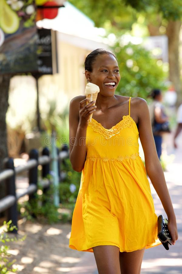 Beautiful woman eating ice cream on street stock photo