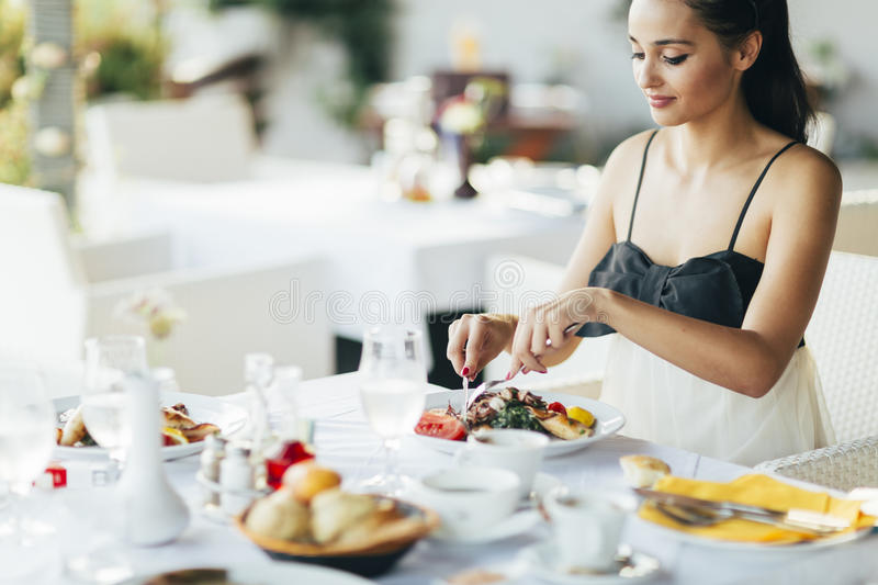 Beautiful woman eating meal in restaurant. During sunset royalty free stock images