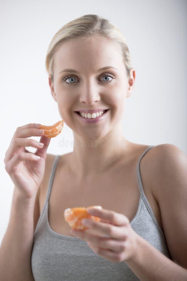 Beautiful woman eating orange royalty free stock photos