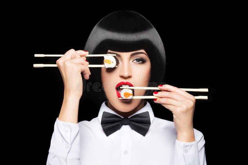 Beautiful woman eating sushi with chopsticks. On black royalty free stock photo