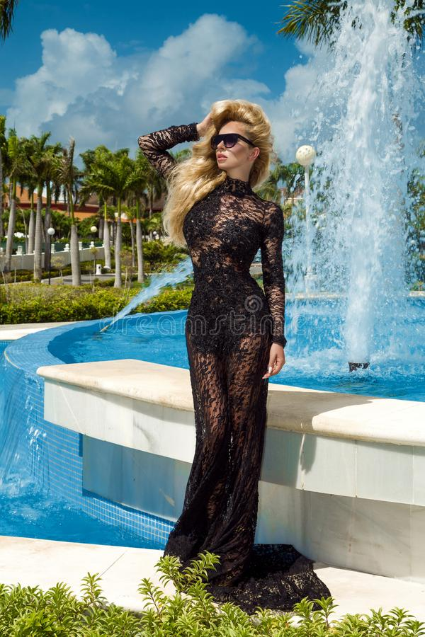 Beautiful woman in an elegant evening gown, stands against the background of a fountain in the Caribbean royalty free stock images