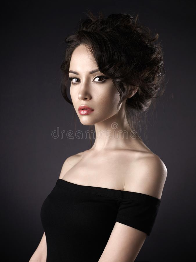 Beautiful woman with elegant hairstyle on black background stock photography