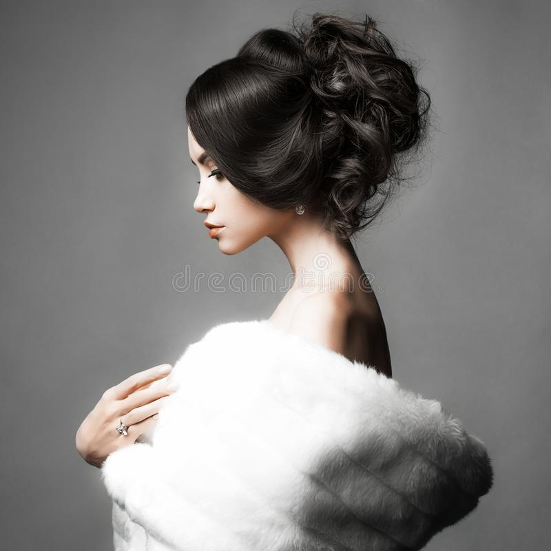 Beautiful woman with elegant hairstyle in white fur coat royalty free stock photo