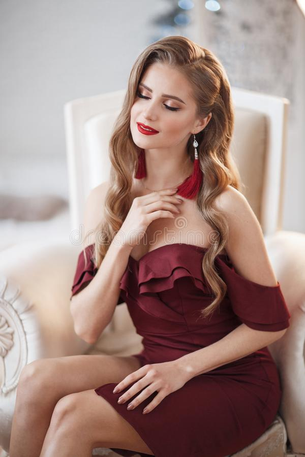 Beautiful woman in an elegant outdoor dress posing alone, sitting in a chair. Beautiful lady in an elegant burgundy dress. Close up fashion portrait of model royalty free stock photos