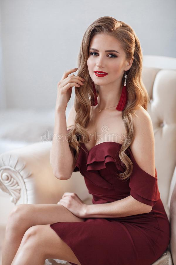 Beautiful woman in an elegant outdoor dress posing alone, sitting in a chair. Beautiful lady in an elegant burgundy dress. Close up fashion portrait of model stock image