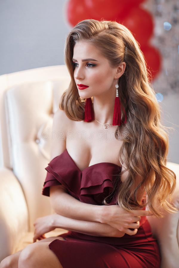 Beautiful woman in an elegant outdoor dress posing alone, sitting in a chair. Beautiful lady in an elegant burgundy dress. Close up fashion portrait of model stock photo