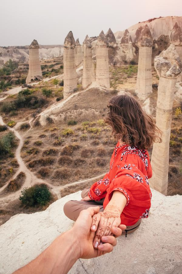 Follow me travel to love valley canyon in Cappadocia, Turkey. Beautiful woman enjoying amazing view of love valley canyon in Cappadocia landscape. Travel in royalty free stock photography