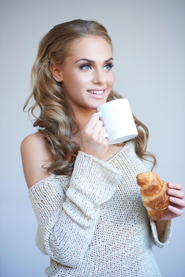 Beautiful woman enjoying a coffee break. Standing looking up with a smile holding a mug of hot coffee in one hand and a freshly baked croissant in the other stock image