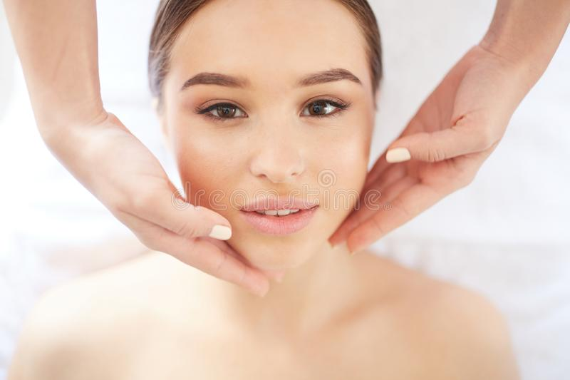 Beautiful Woman Enjoying Facial Massage in SPA. Above view portrait of beautiful young women looking at camera enjoying face and neck massage in SPA , closeup royalty free stock images