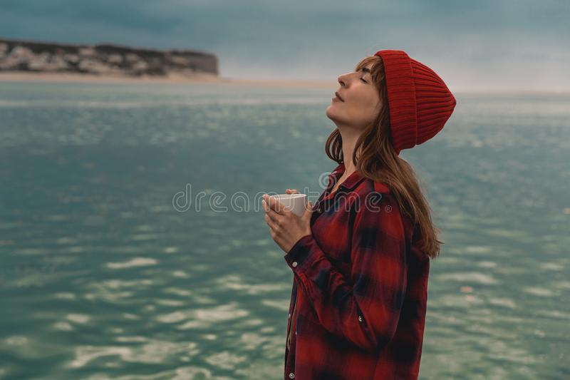 Me and my Coffee. Beautiful woman enjoying her day in the lake with a mug of hot coffee royalty free stock photos