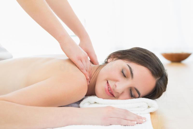 Beautiful woman enjoying neck massage at beauty spa. Close up of a beautiful woman enjoying neck massage at beauty spa royalty free stock photography