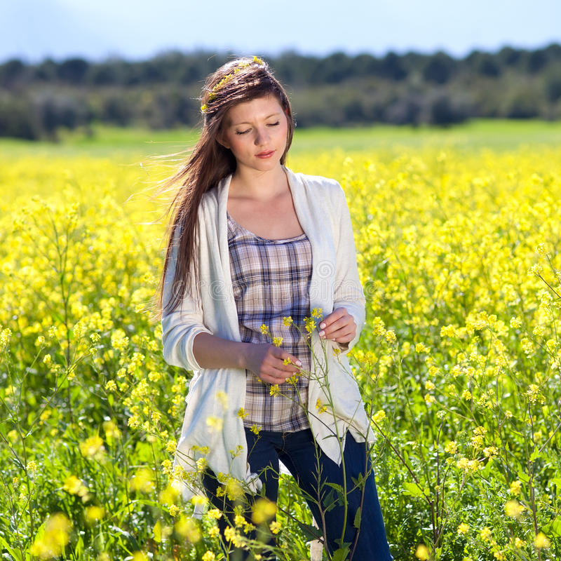 Beautiful woman enjoying the tranquility of nature. Beautiful young woman enjoying the tranquility of nature as she stands in a field of golden rapeseed flowers royalty free stock images