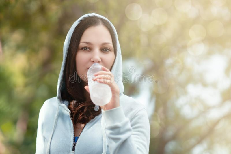 Beautiful woman enjoys drinking water during exercise. stock images