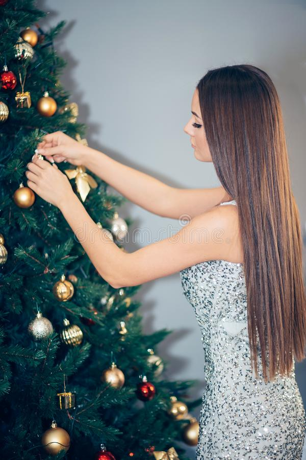 Beautiful woman in evening dress near the luxury decorated Christmas tree. New Year`s holidays at home royalty free stock photography