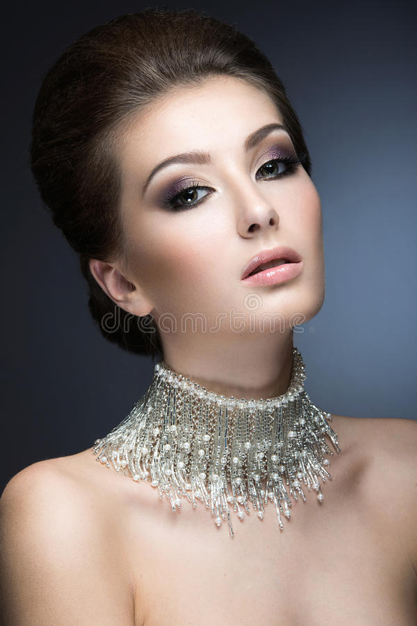Beautiful woman with evening make-up and hairstyle and a large necklace around her neck. Beauty face. royalty free stock image