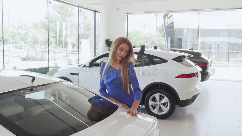 Beautiful woman examining expensive car at the dealership royalty free stock image