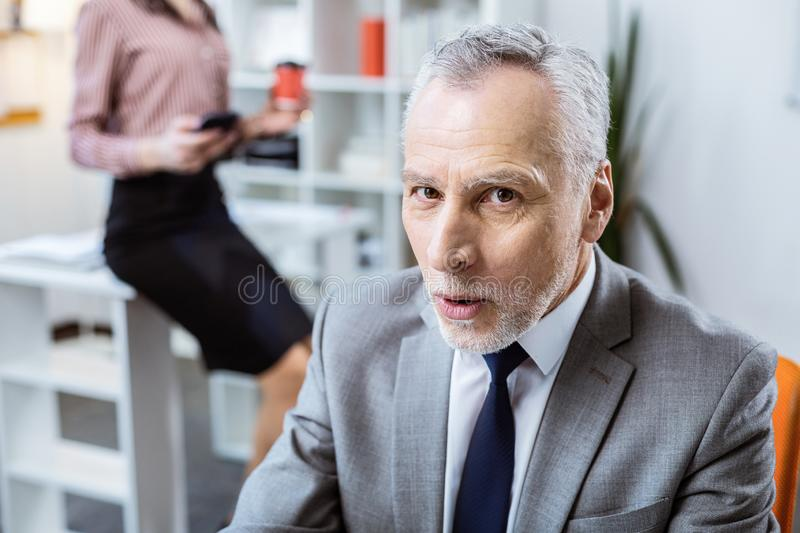 Excited grey-haired man with stubble being happy. Beautiful woman. Excited grey-haired men with stubble being happy while working near curvy woman stock images