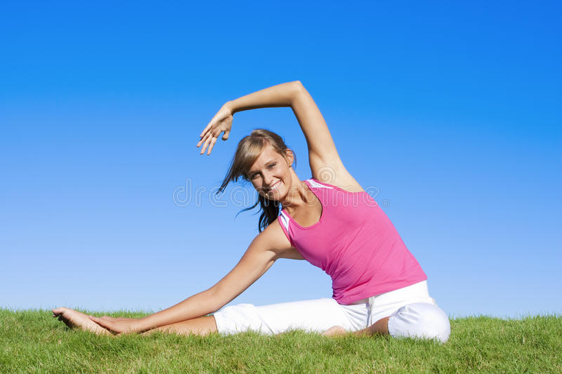 Beautiful Woman Exercising. An attractive woman stretching before her workout royalty free stock image