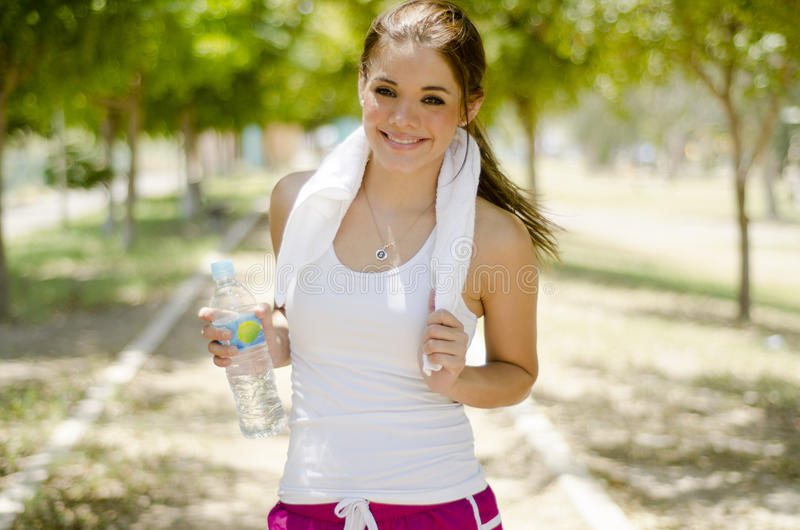 Beautiful woman exercising. Young beautiful woman taking a break from running at the park royalty free stock image