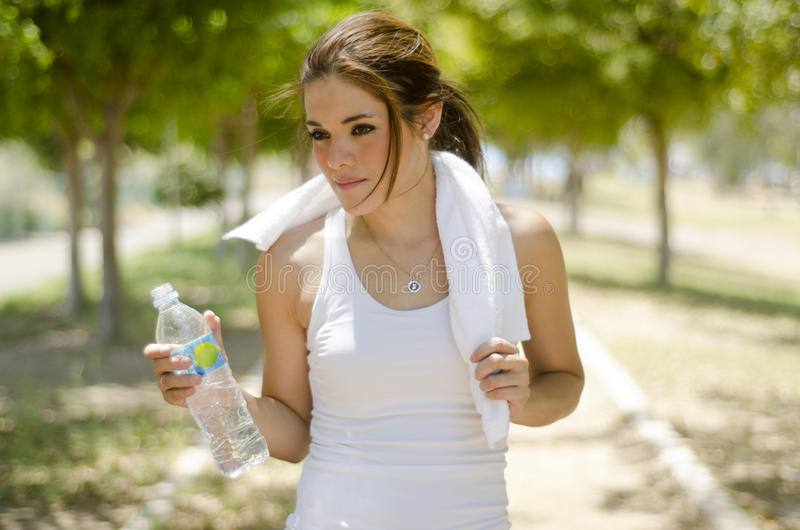 Beautiful woman exercising. Young beautiful woman taking a break from running at the park stock images